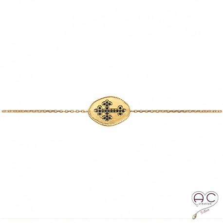Bracelet la croix sertie de zircon noir sur médaile ovale en plaqué or satiné, avec une chaîne fine